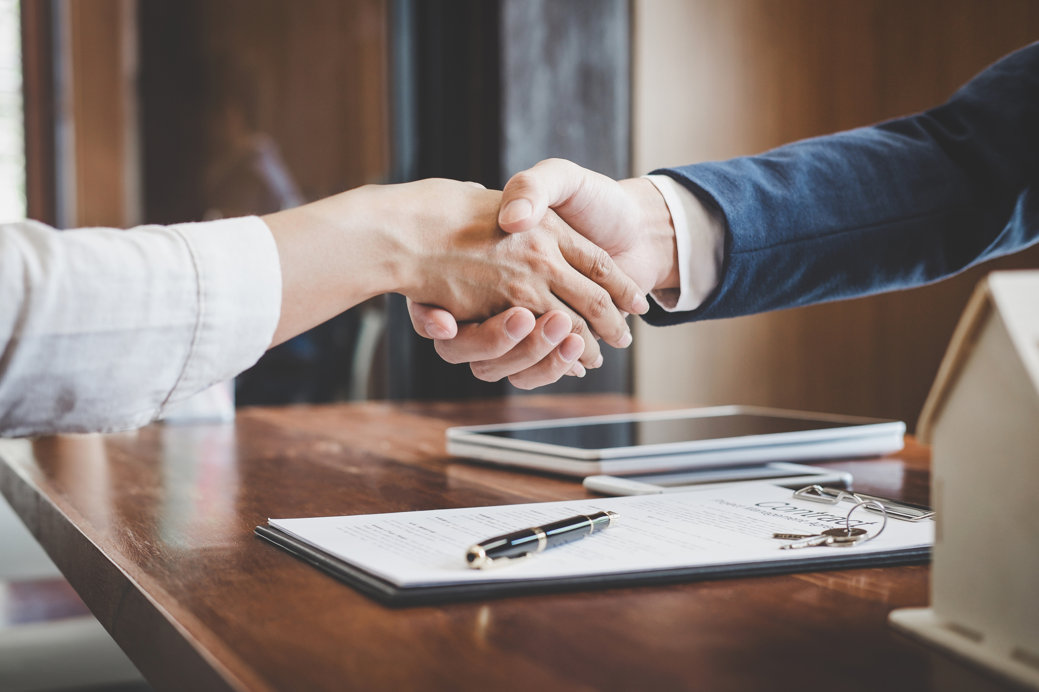 Two people shaking hands over paperwork to form a tax entity structure for investing in real estate